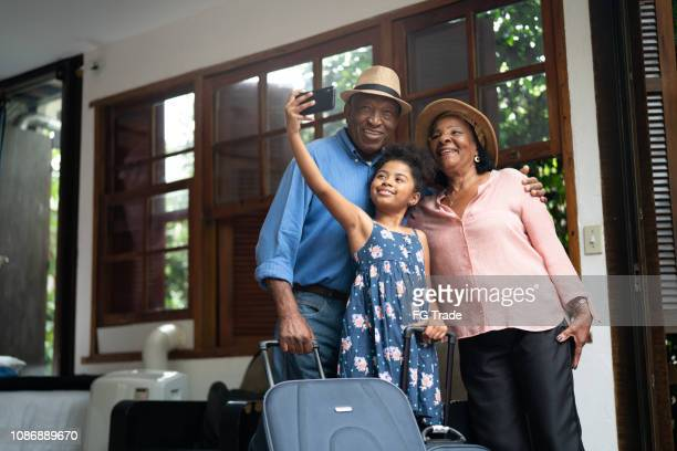 grandparents and granddaughter taking selfies after arriving in a hotel - african american family home stock photos and pictures