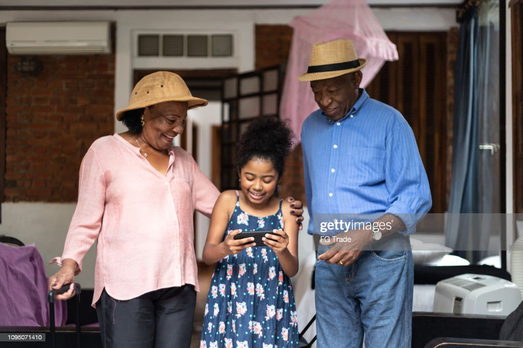 Grandparents and granddaughter using mobile phone in the room : Stock Photo