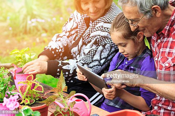 Grandparents and granddauther in the garden-side view