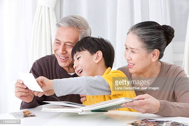 grandparents and grandson looking through family album - asian granny pics stock photos and pictures