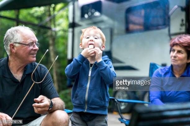grandparents and grandson roasting marshmallow over campfire in camping in summer - camper trailer stock pictures, royalty-free photos & images