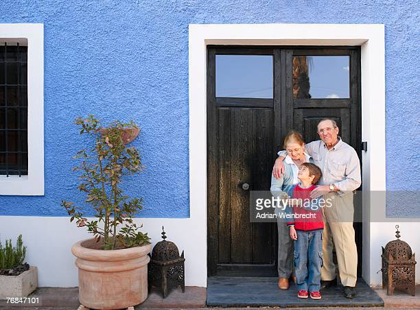 Grandparents and grandson (6-8) standing at front door, smiling
