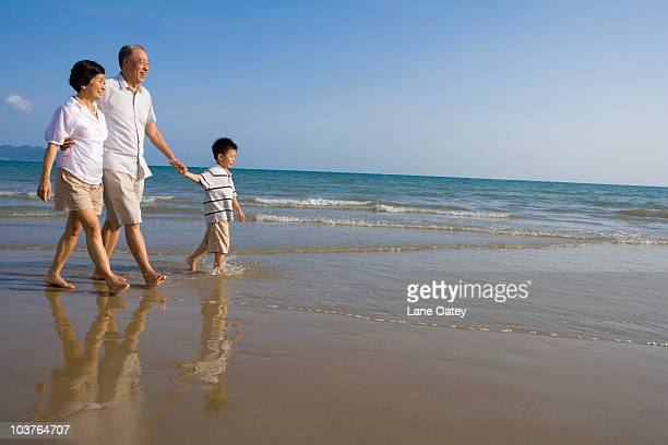 Grandparents and grandson walking along the beach