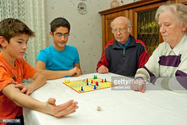 grandparents and grandsons playing a board game / families / people / children / kids / boys / teenagers