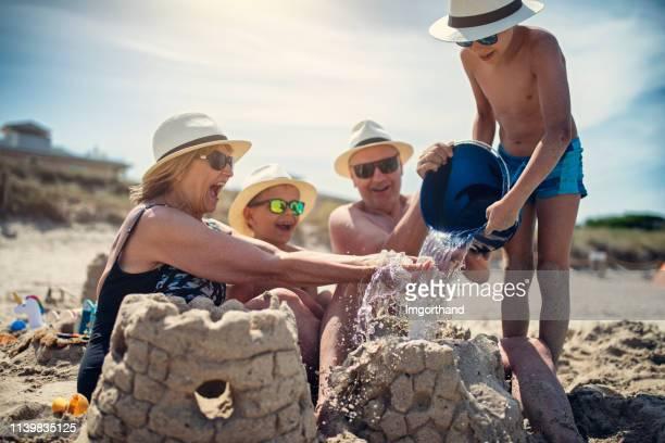 grands-parents et petits-fils jouant ensemble dans le sable sur la plage - vacances à la mer photos et images de collection