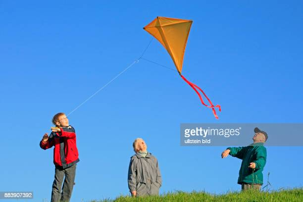grandparents and their grandson are flying a selfmade kite together / families / family / people / children / kids / boy / grandad / grandpa / autumn...