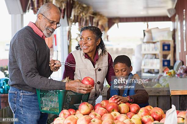 grandparents and their grandson choosing apples - apple fruit stock photos and pictures