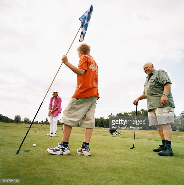 grandparents and their grandson play on a golf course - fat granny stock pictures, royalty-free photos & images