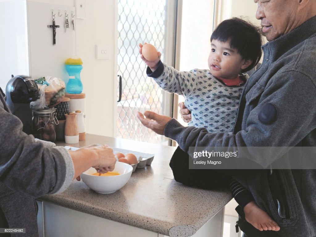 grandparents are whisking an egg and preparing breakfast with toddler : Stock Photo
