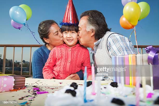 Grandparents celebrating birthday of granddaughter