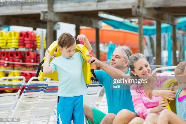 abuelos, los niños ponen en chalecos salvavidas en el parque del agua - life jacket photos fotografías e imágenes de stock