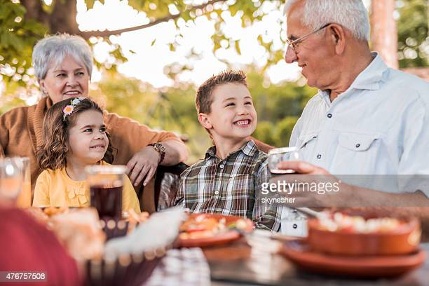 Grandparents communicating with grandchildren during lunch in restaurant.