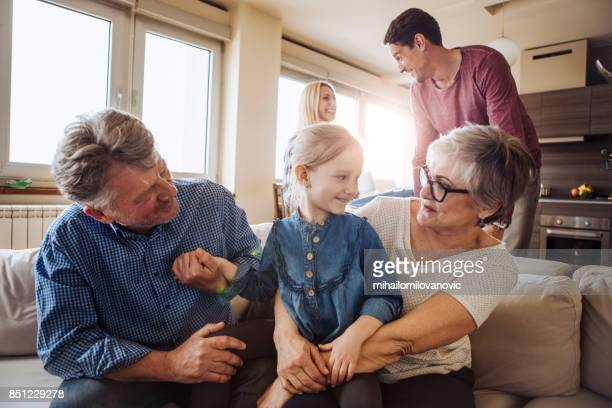 Grandparents cuddling granddaughter