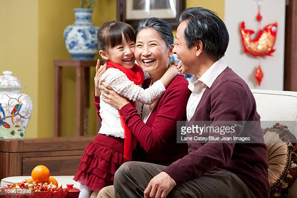Grandparents embracing granddaughter during Chinese New Year