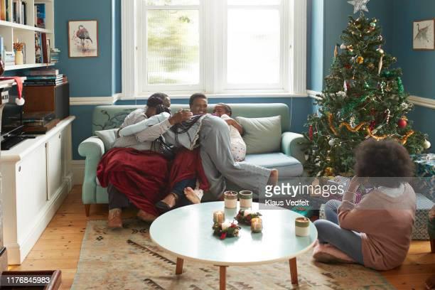 Grandparents embracing granddaughters at home