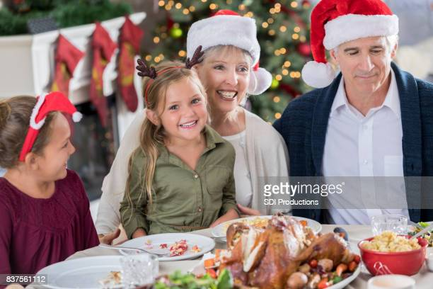Grandparents enjoy Christmas meal with young granddaughters