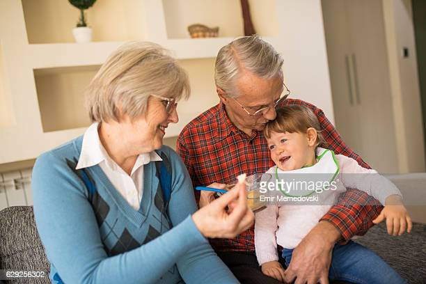 Grandparents feeding their adorable granddaughter