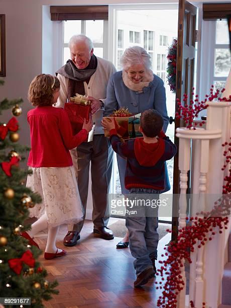 Grands-parents et petits-enfants pour des cadeaux de Noël à la porte