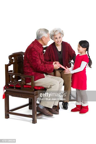 Grandparents giving red pocket to granddaughter