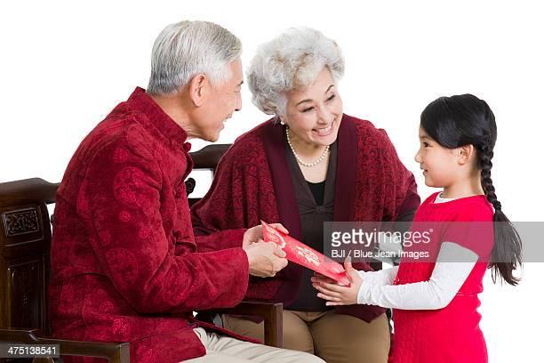 Grandparents giving red pocket to granddaughter