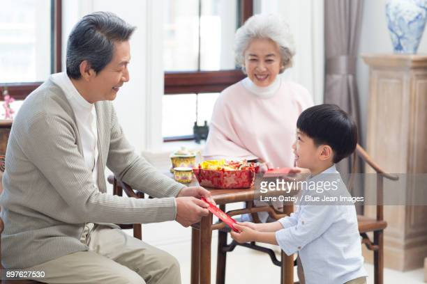 Grandparents giving red pockets to grandson