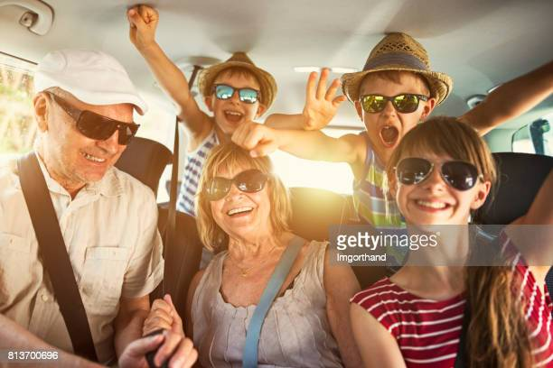 grandparents having fun on road trip with grandchildren - family inside car stock photos and pictures