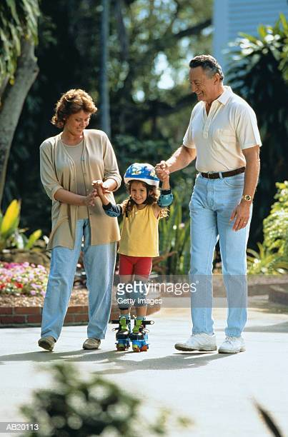 Grandparents helping granddaughter (4-6) to rollerskate