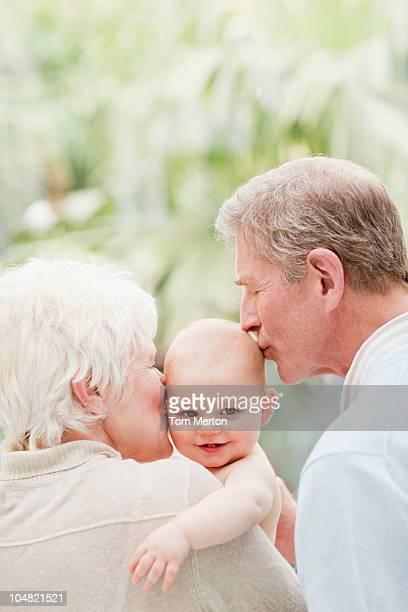 Großeltern halten und küssen lächelnden baby