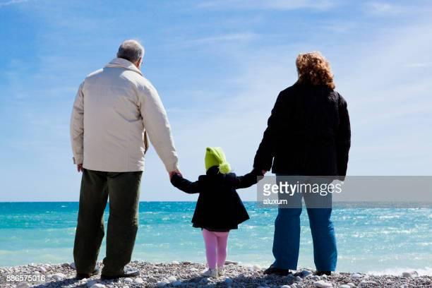 Grands-parents, main dans la main avec la petite fille en regardant la mer
