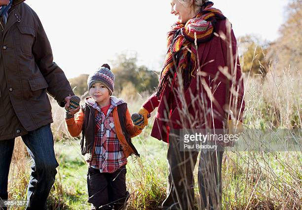 Grandparents holding hands with grandson outdoors