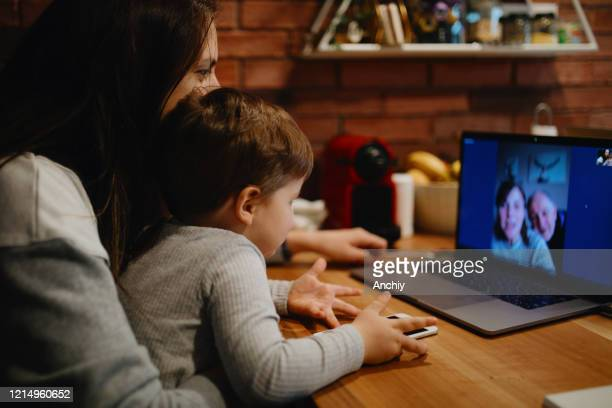 grandparents in quarantine at home having video call with grandson and daughter - facetime stock pictures, royalty-free photos & images