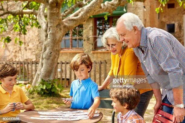 avós, olhando para o cartão de jogo de crianças - carta de baralho jogo de lazer - fotografias e filmes do acervo