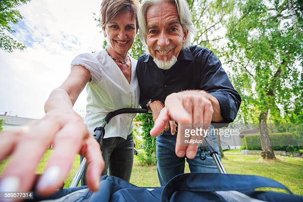 Grandparents looking at their grandchild in baby stroller, POV