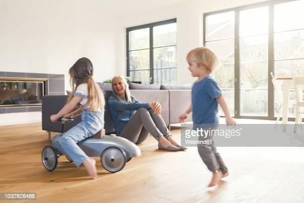 Grandparents observing grandmother, playing in livingroom