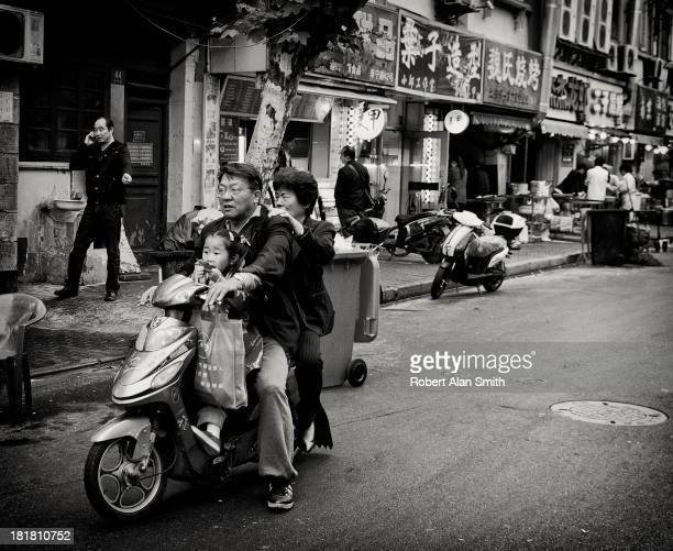 Grandparents on an electric scooter out on a shopping trip with their granddaughter in the streets on Shanghai