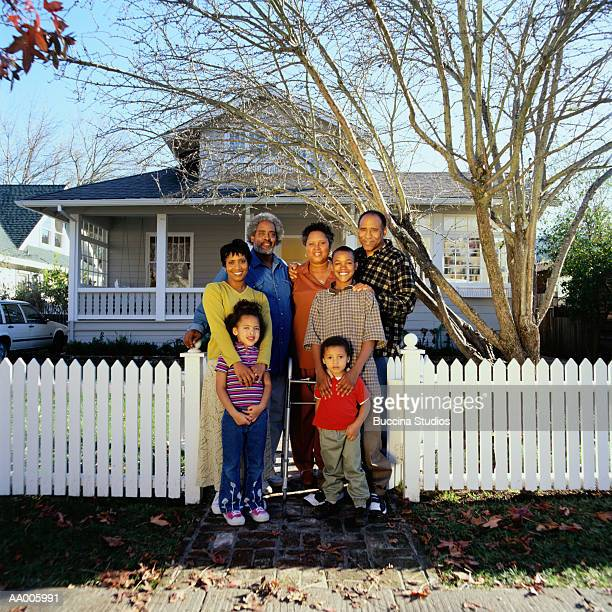 Grandparents, parents and children (3-12) in front of house, portrait
