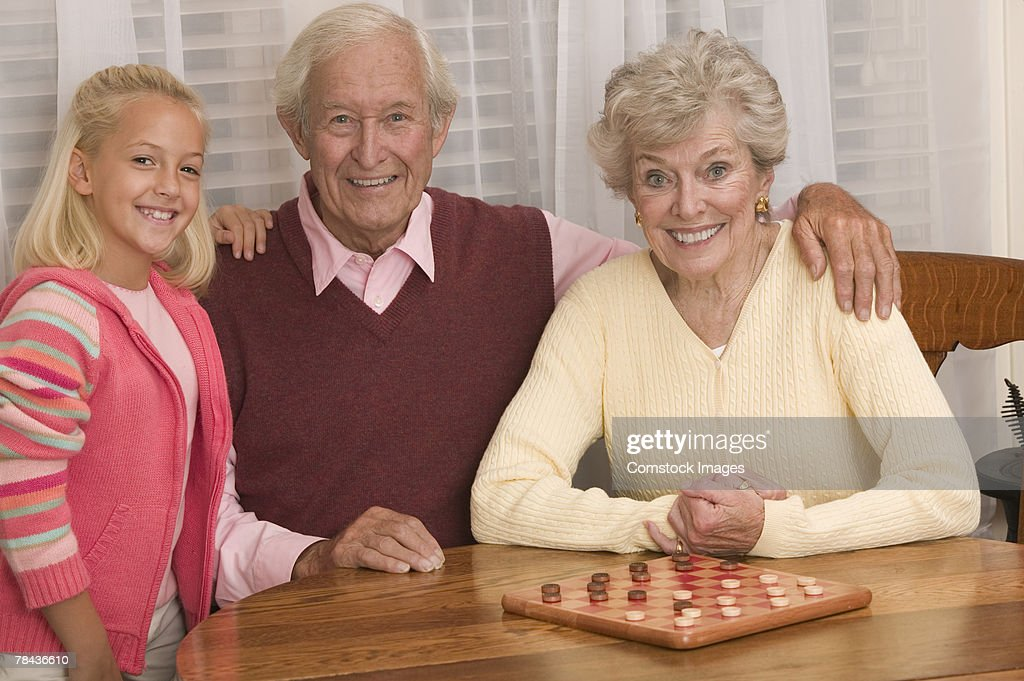 Grandparents playing checkers with granddaughter : Stockfoto