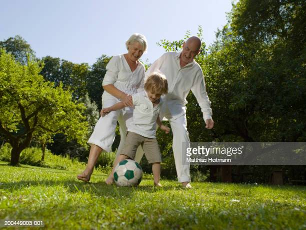 Grandparents playing football in garden with grandson (3-5) smiling