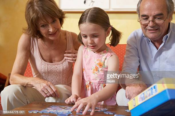 Grandparents playing jigsaw puzzle with granddaughter (6-8)