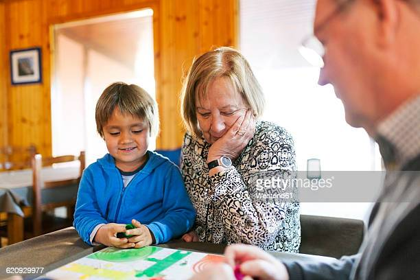 Grandparents playing ludo their grandson