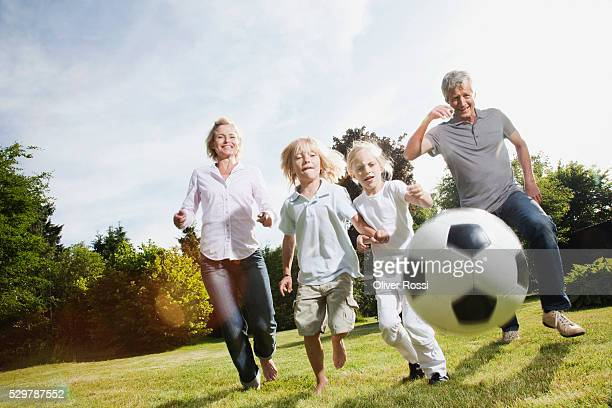 Grandparents playing soccer with grandchildren