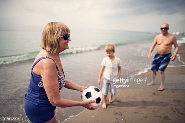 Grandparents playing soccer with grandson on beach