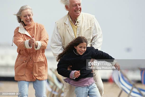 grandparents playing with granddaughter (8-10) at beach - girl blows dog stock photos and pictures
