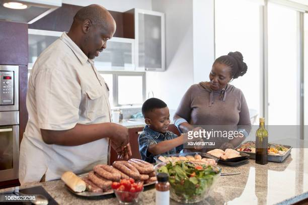 grandparents preparing food with grandson at home - generation gap stock photos and pictures