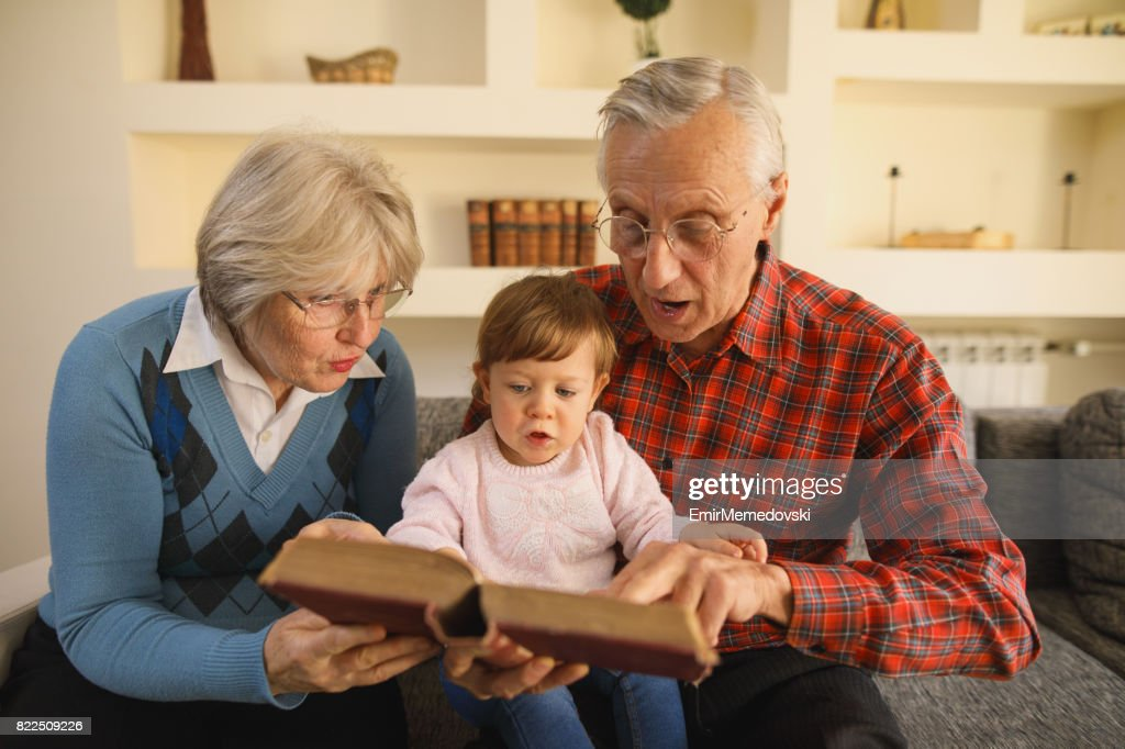 Grandparents reading a book to their granddaughter : Stock Photo