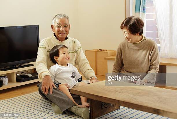 Grandparents relaxing with grandson in living room
