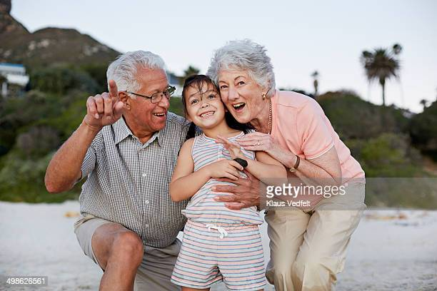 Grandparents showing grandchild birds on the beach