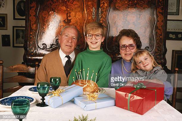 Grandparents sitting with grandchildren (4-9) by candlelit cake