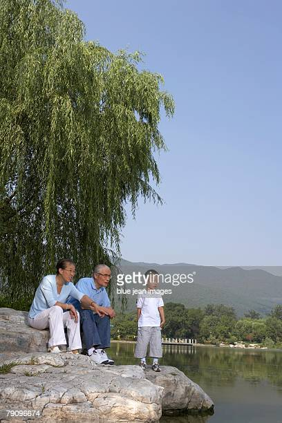 Grandparents spending quality time with their grandson alongside a scenic lake.