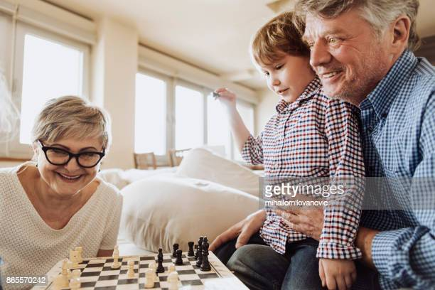 grandparents spending time with grandson - game board stock photos and pictures